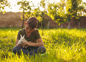 Cute boy holding a little white bunny at nature