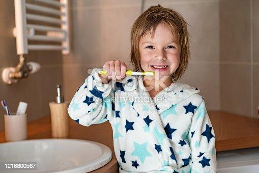948443044 istock photo Cute boy holding toothbrush 1216800567