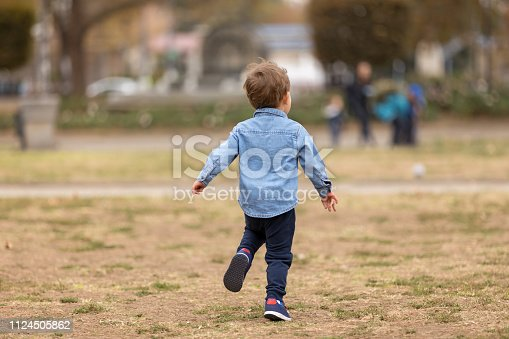 Cute boy in blue shirt running away from the camera in the park. Selective focus.