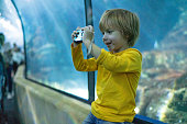 Sweet boy is taking photos in public aquarium