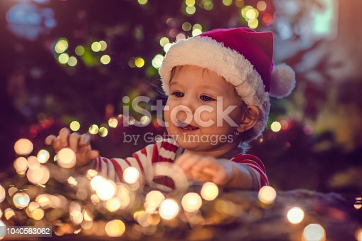 Child playing with lights near Christmas tree