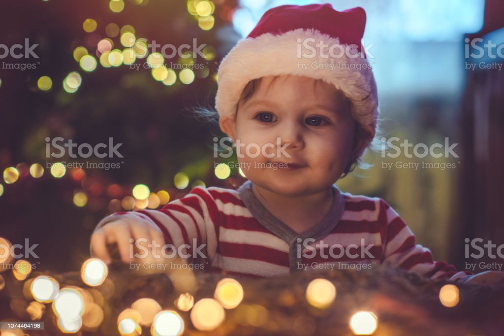 Cute boy indoors near Christmas tree stock photo