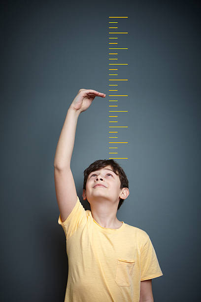 Cute boy is showing height on a wall scale - Photo