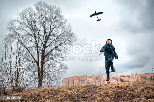 A boy is throwing toy airplane to the sky. He is dressed in casual clothes and rubber boots. The boy is jumping from the hillock and looking up at the flying homemade glider. Shooting at overcast spring day in a countryside near town