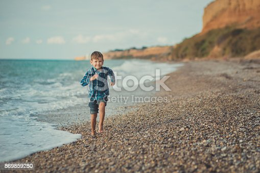 873786782istockphoto Cute boy kid child wearing stylish shirt and blue jeans barefoot posing running on stone beach with gorgeous ocean sea landscape sand cliff cape 869859280