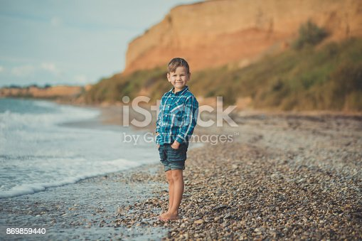 873786782istockphoto Cute boy kid child wearing stylish shirt and blue jeans barefoot posing running on stone beach with gorgeous ocean sea landscape sand cliff cape 869859440