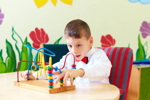 cute boy, kid in wheelchair solving logical puzzle in rehabilitation center for children with special needs - foto stock
