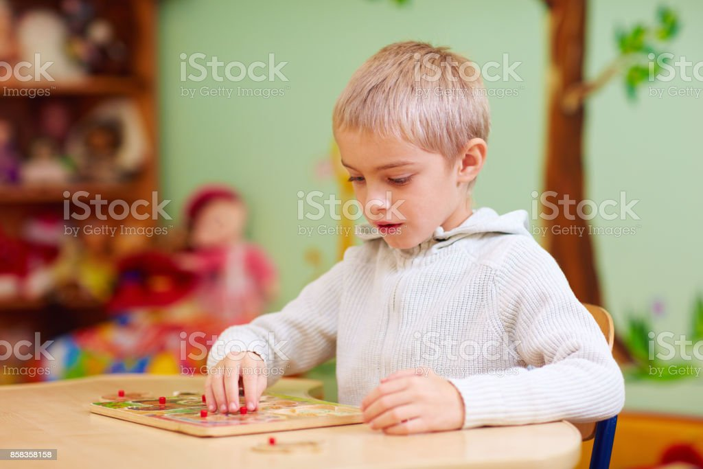 cute boy, kid with special needs solving a puzzle in rehabilitation center stock photo