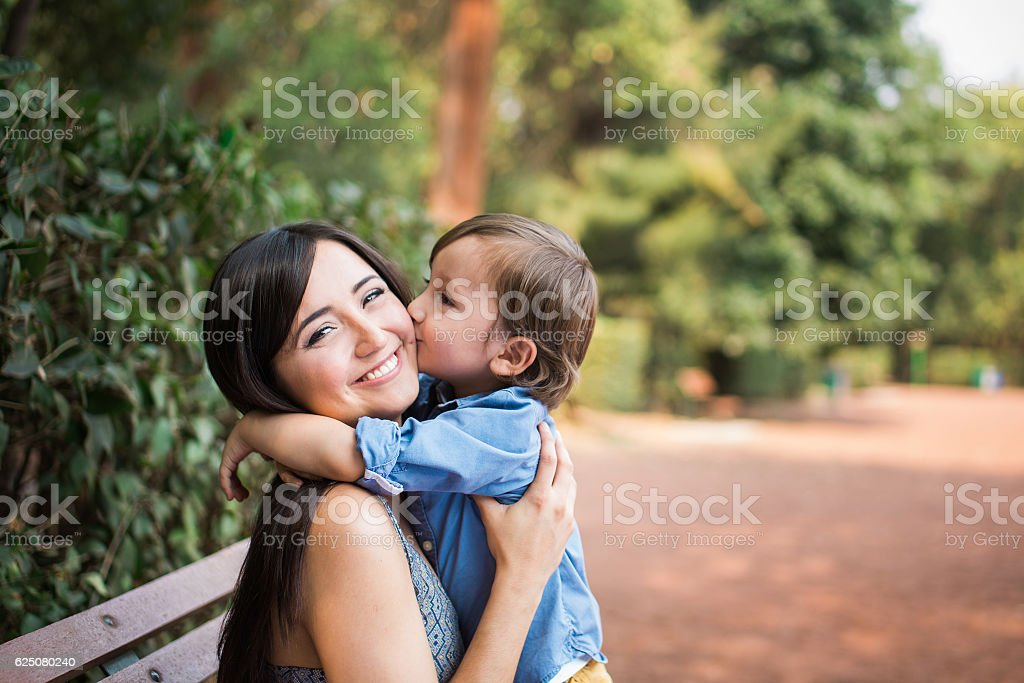 Cute boy kissing mother on the cheek stock photo