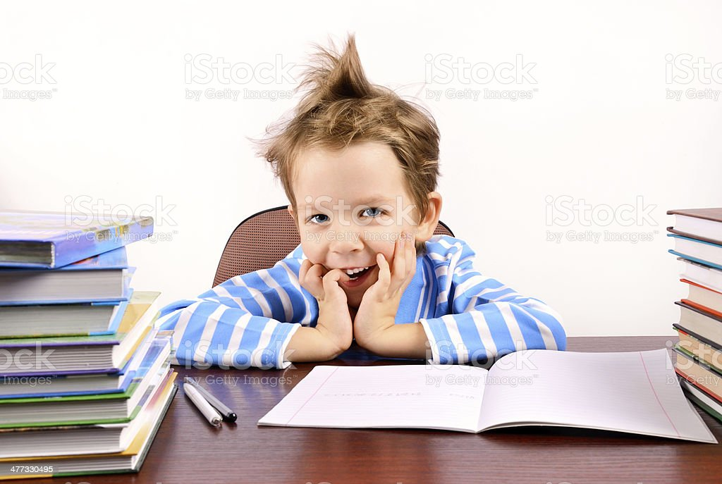 cute boy laughing sitting at the desk royalty-free stock photo