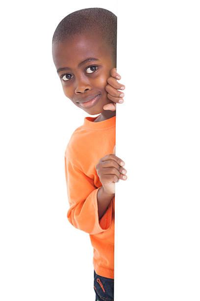 süße junge schaut um die ecke - peeping tom stock-fotos und bilder