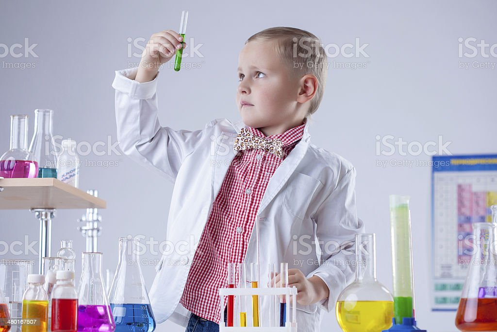 Cute boy looking at color of reagent in test-tube stock photo