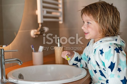 948443044 istock photo Cute boy looking at his smile in the mirror 1224830061
