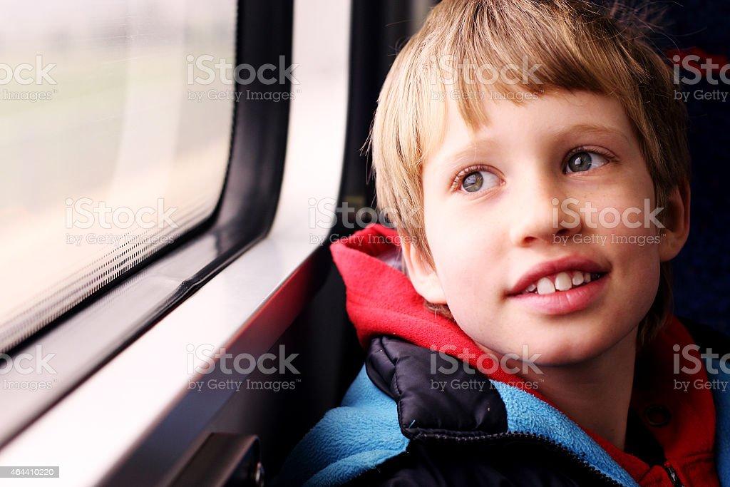 Cute Boy looking through the window stock photo