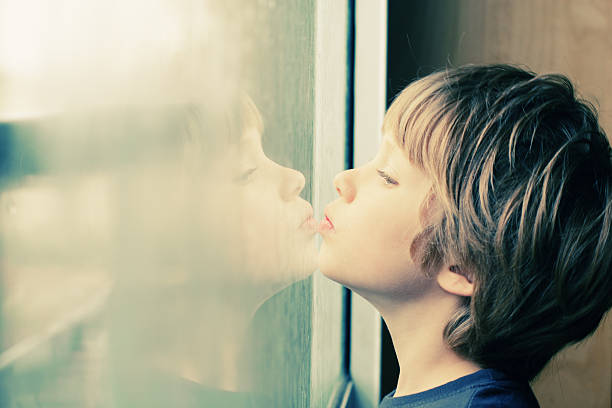 Cute boy looking through the window Cute 6 years old boy looking through the window autism stock pictures, royalty-free photos & images