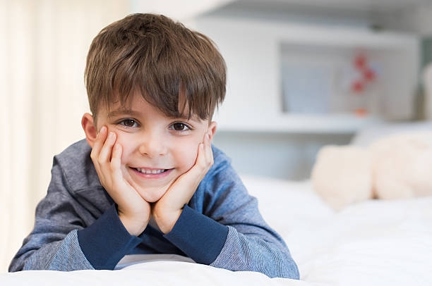 Cute boy lying on bed stock photo
