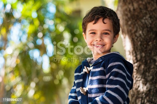 Cute boy enjoying the outdoors sitting in a tree.