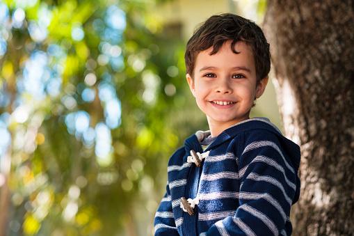 Cute boy enjoying the outdoors sitting in a tree.