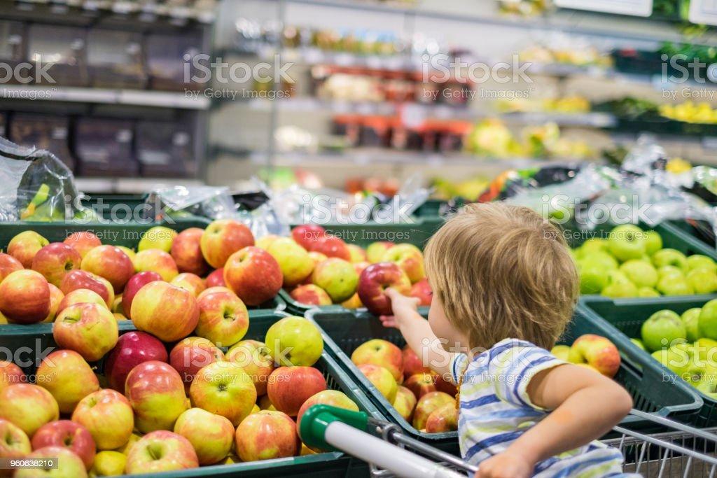 Apple de colheita menino bonitinho na loja - foto de acervo