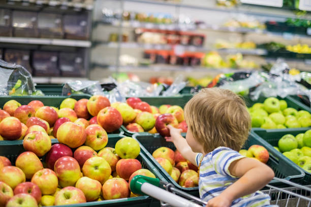 Cute boy picking apple in the store Small cute boy taking apple in supermarket produce aisle stock pictures, royalty-free photos & images