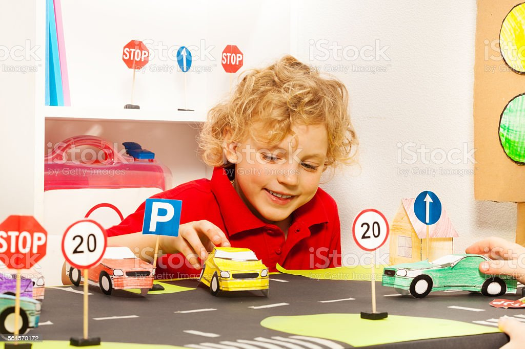 Cute boy playing driver with toy paper cars stock photo