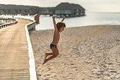 istock Cute boy playing on beach pier 1273762776