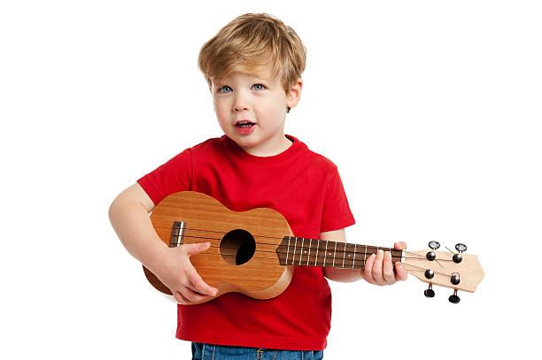 süßer junge spielt wie man ukulele spielt gitarre - ukulele songs stock-fotos und bilder
