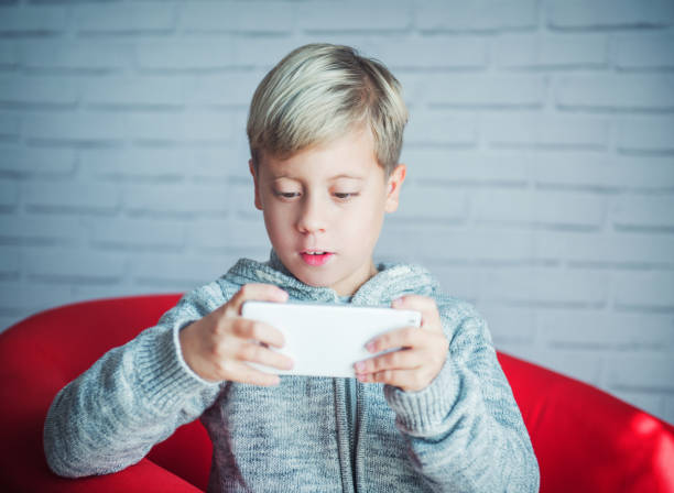 Cute boy playing with a smartphone – Foto
