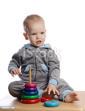 istock cute boy playing with color pyramid toy 636307490