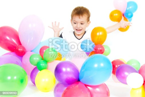 istock cute boy playing with colorful balloons over white 95509550