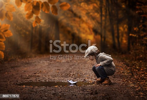 Little boy playing with the paper boat in the autumn forest puddle