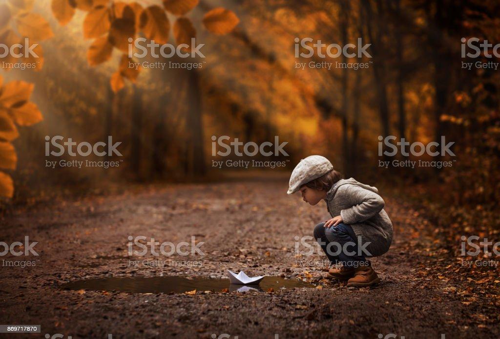 Menino bonito, jogando com o barquinho de papel - foto de acervo