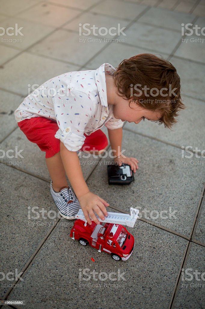 Cute boy playing with remote controlled truck on the street. stock photo