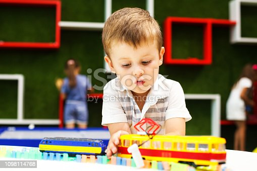 istock Cute boy playing with tram. Little boy playing with car toy. 1098114768