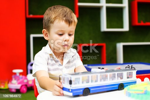 istock Cute boy playing with trolley car. Developing toys. 1097864972