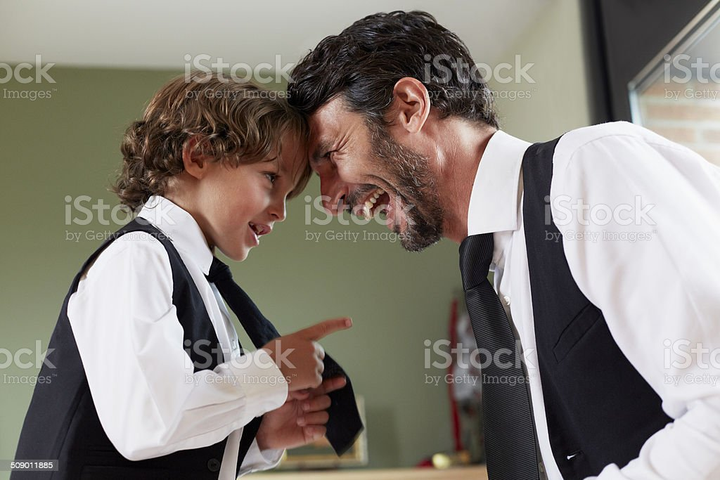 Cute boy pointing at happy father stock photo