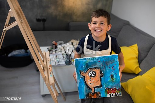 A cute boy is standing next to an easel in his  living room holding a portrait he painted and smiling proudly
