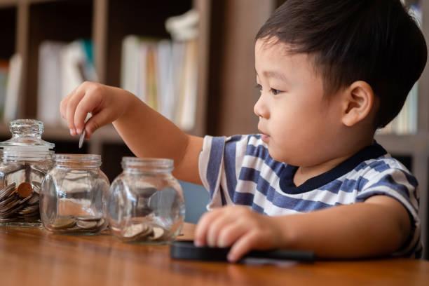 niedlichen Jungen setzen Geldmünzen in Glas, Sparen Geld Konzept – Foto