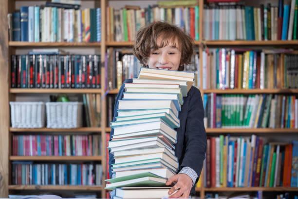 Cute boy reading book in library – zdjęcie