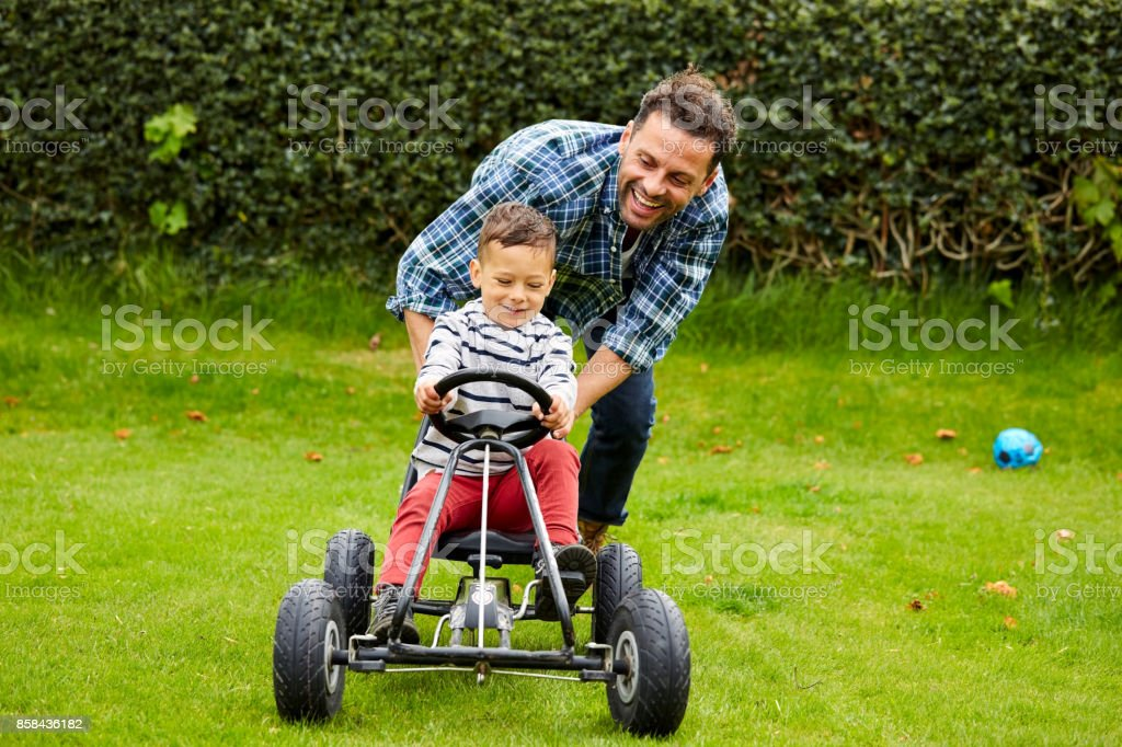 Cute boy riding pedal car with father in garden stock photo