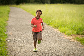 Smiling boy running happy on a gravel walk. He is wearing an orange shirt and shorts and he's from Ethiopia.