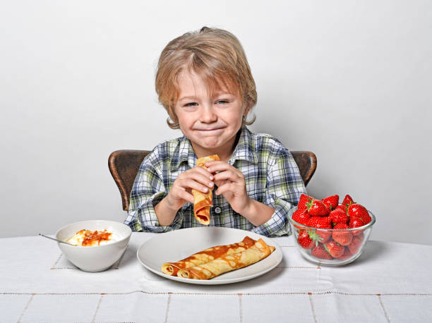 Cute Boy sitting at breakfast table eating pancakes and strawberries stock photo