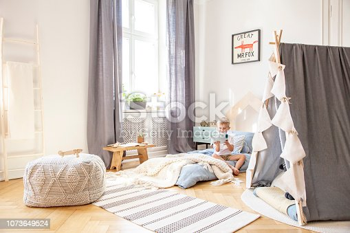 1205865899 istock photo Cute boy sitting on bed in scandinavian bedroom interior with tent and big comfortable pouf, real photo 1073649524