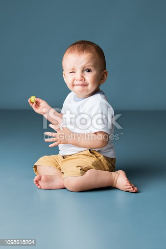 A cute latin baby boy sitting on the floor barefoot, looking at the camera and making a face.