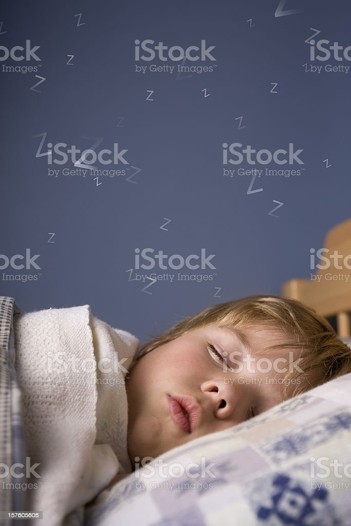Cute boy sleeping in bed stock photo