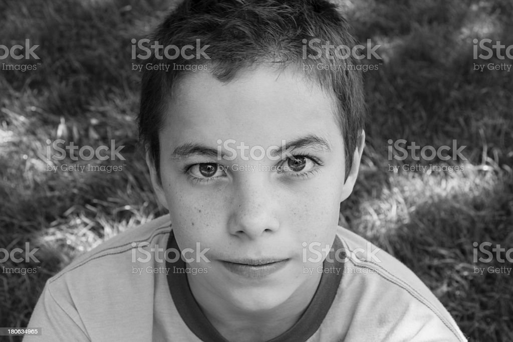 Cute boy smiling at camera in the park royalty-free stock photo