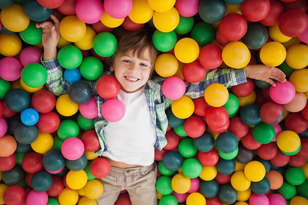 Mignon petit garçon souriant avec piscine à balles - Photo