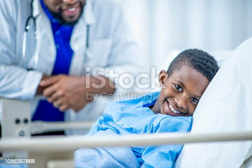 istock Cute boy smiling in his hospital bed 1056397668