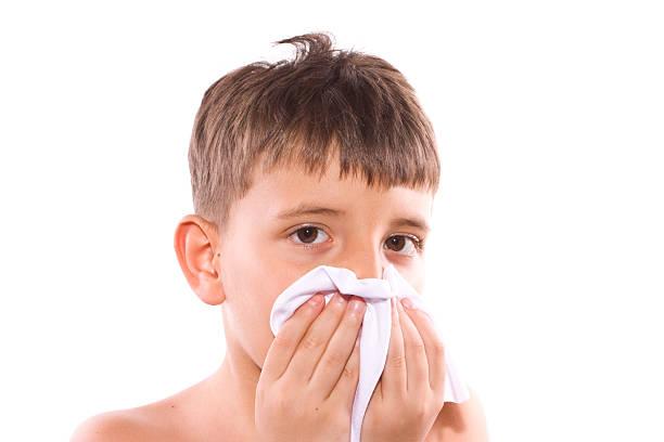 cute boy sneezing stock photo