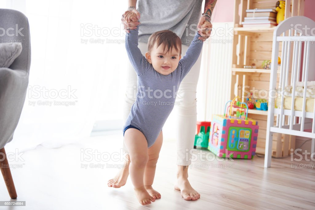 Cute boy taking first steps holding mums hands stock photo